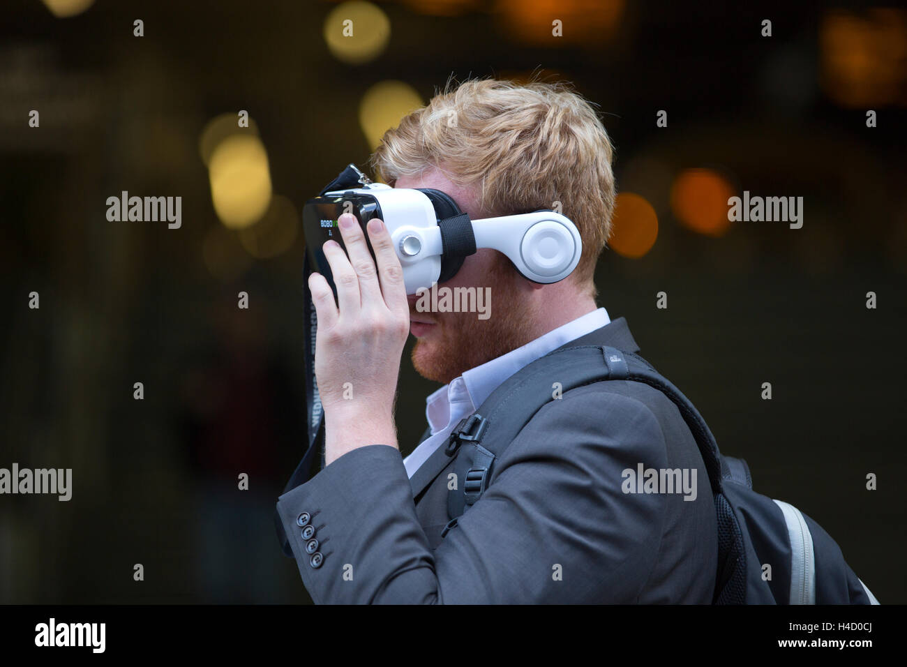 Man wearing Virtual Reality Headset BOBOVR Z4 on the streets of London, UK - Stock Image