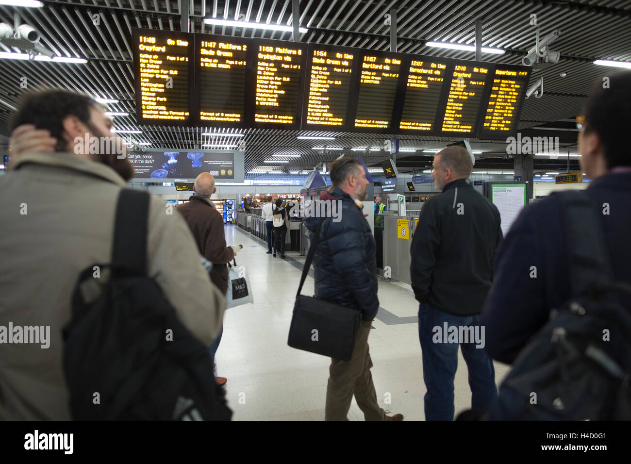 Commuters waiting for train information at London Cannon Street station, Central London, England, United Kingdom - Stock Image