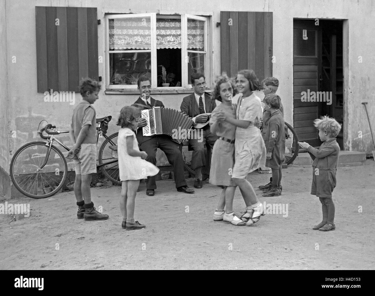 Zwei Männer machen Musik und Kinder tanzen dazu im Hof, Deutschland 1930er Jahre. Two men making music and - Stock Image