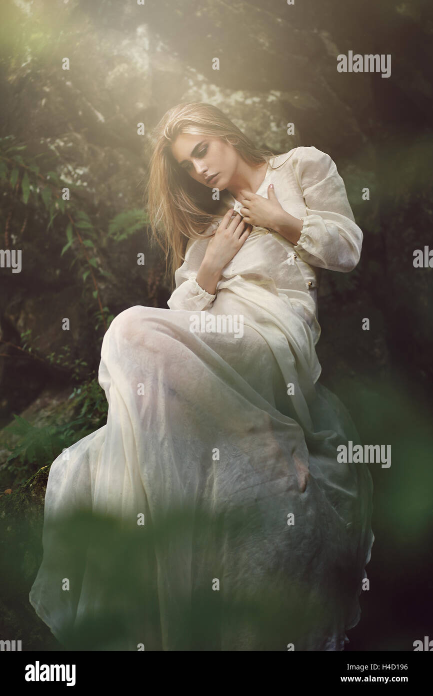 Graceful woman posing in dreamy forest. Ethereal and fantasy - Stock Image