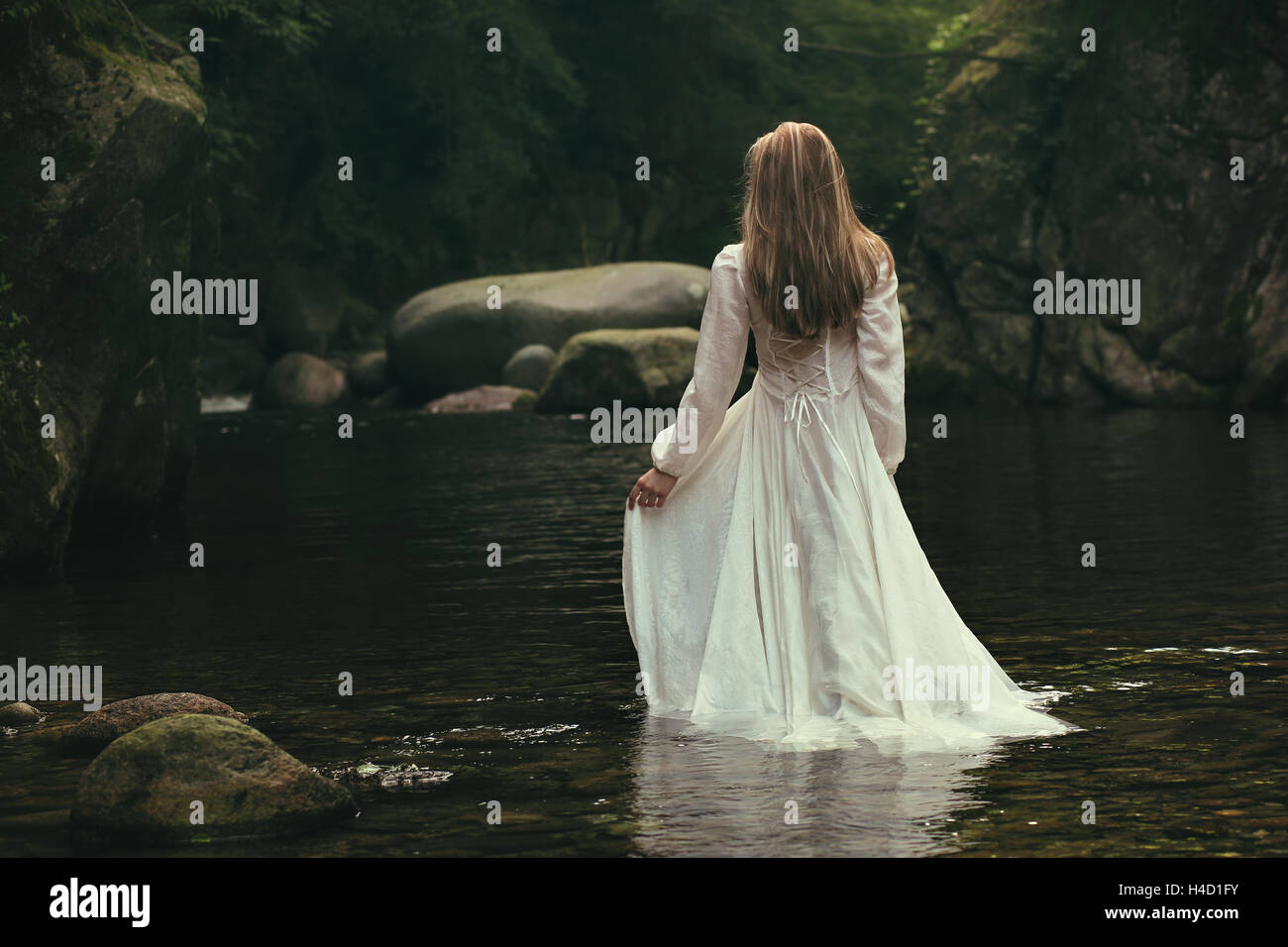 Romantic woman walks into a green stream. Ethereal and dreamy - Stock Image