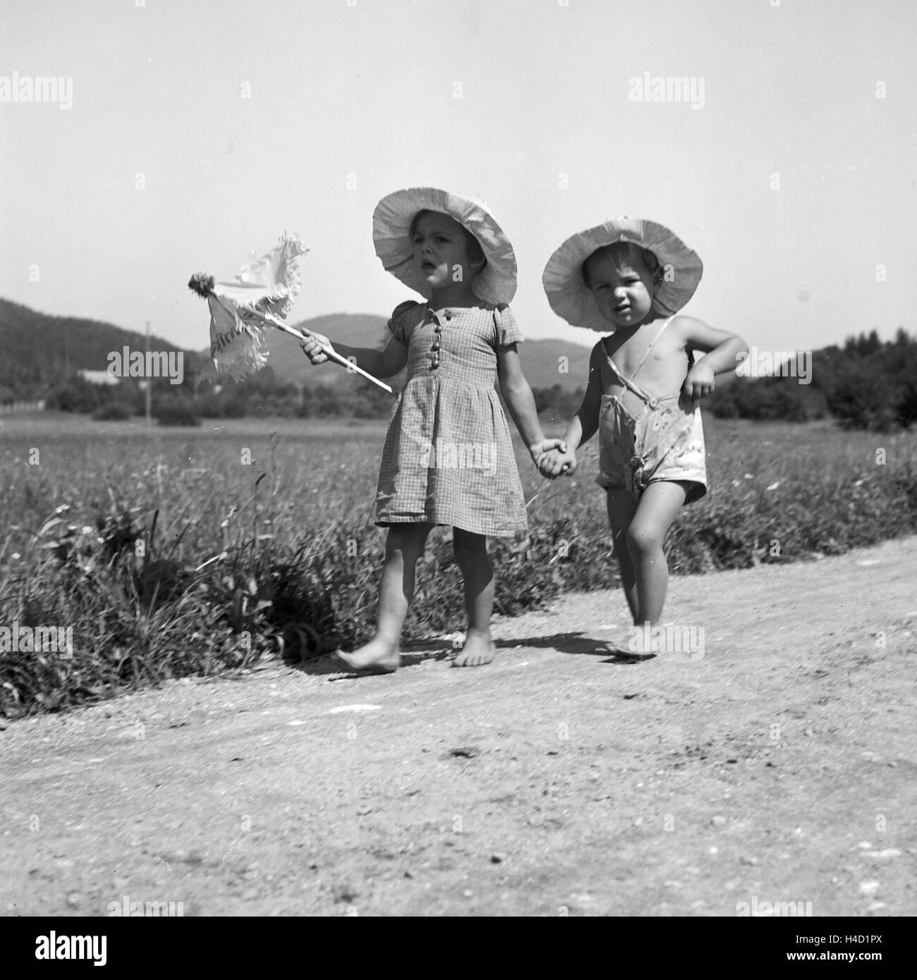 Zwei kleine Kinder bei einem Spaziergang in der Sonne, Deutschland 1930er Jahre. Two toddlers strolling through Stock Photo