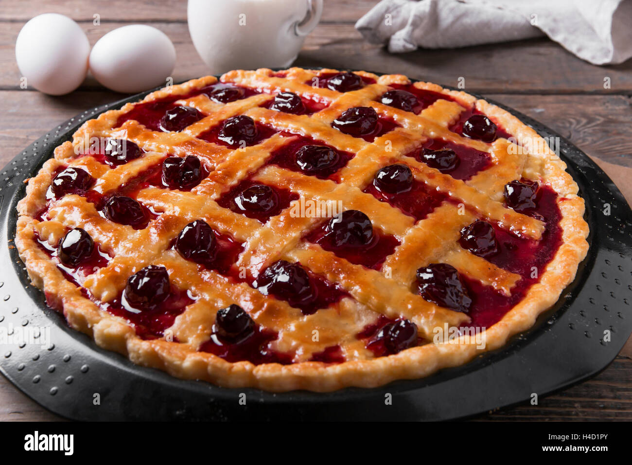 Homemade traditional sweet cherry tart pie with wooden table background. - Stock Image