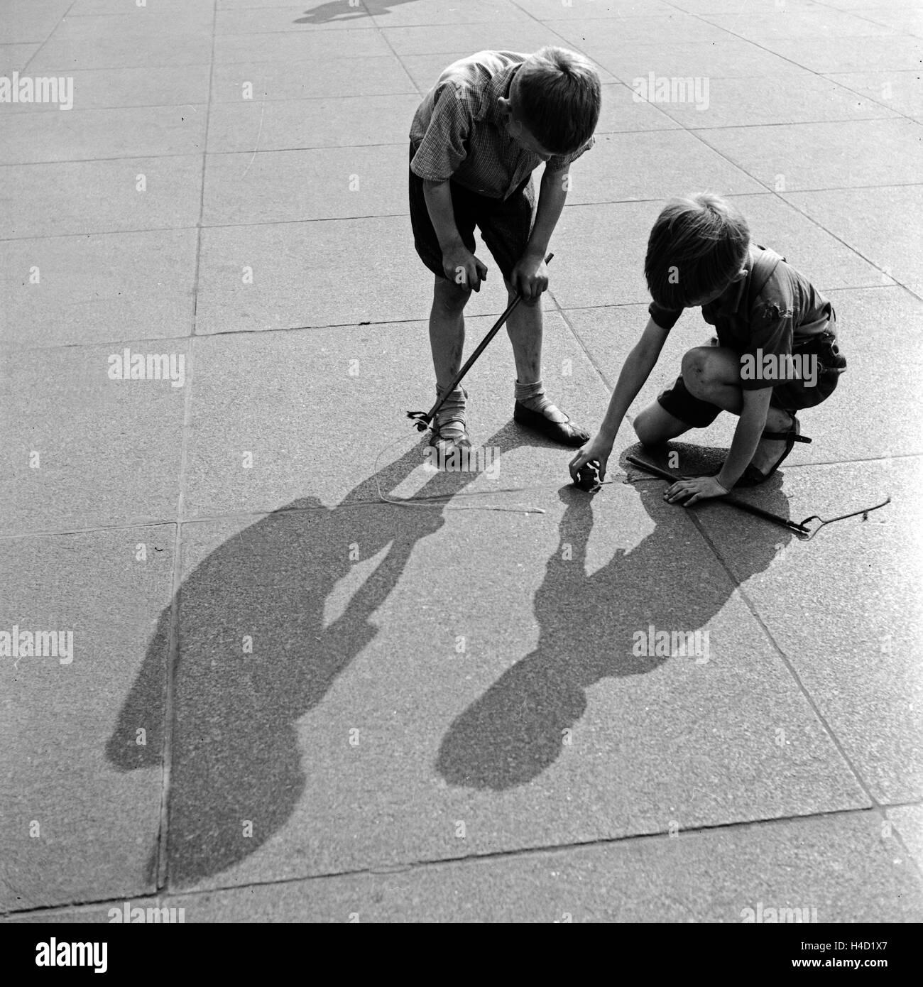 Zwei Jungen spielen Peitschenkreisel auf einem Platz in Bochum, Deutschland 1930er Jahre. Two little boys playing - Stock Image