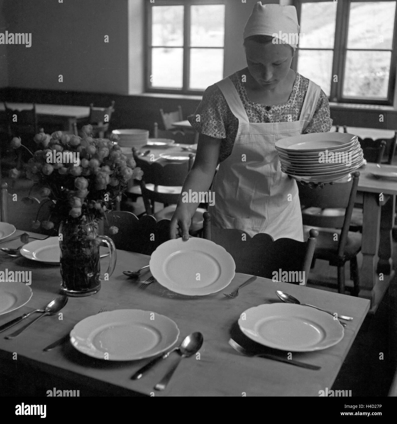 Ein BdM Mädchen beim Tischdecken im Speisesaal in der Haushaltungsschule Greifenberg, Deutschland 1930er Jahre. Stock Photo