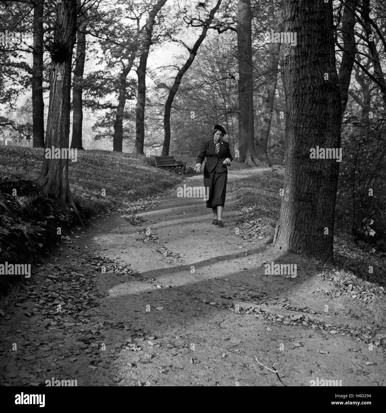 Eine Frau bei einem herbstlichen Spaziergang durch einen Park, Deutschland 1930er Jahre. A woman strolling through - Stock Image