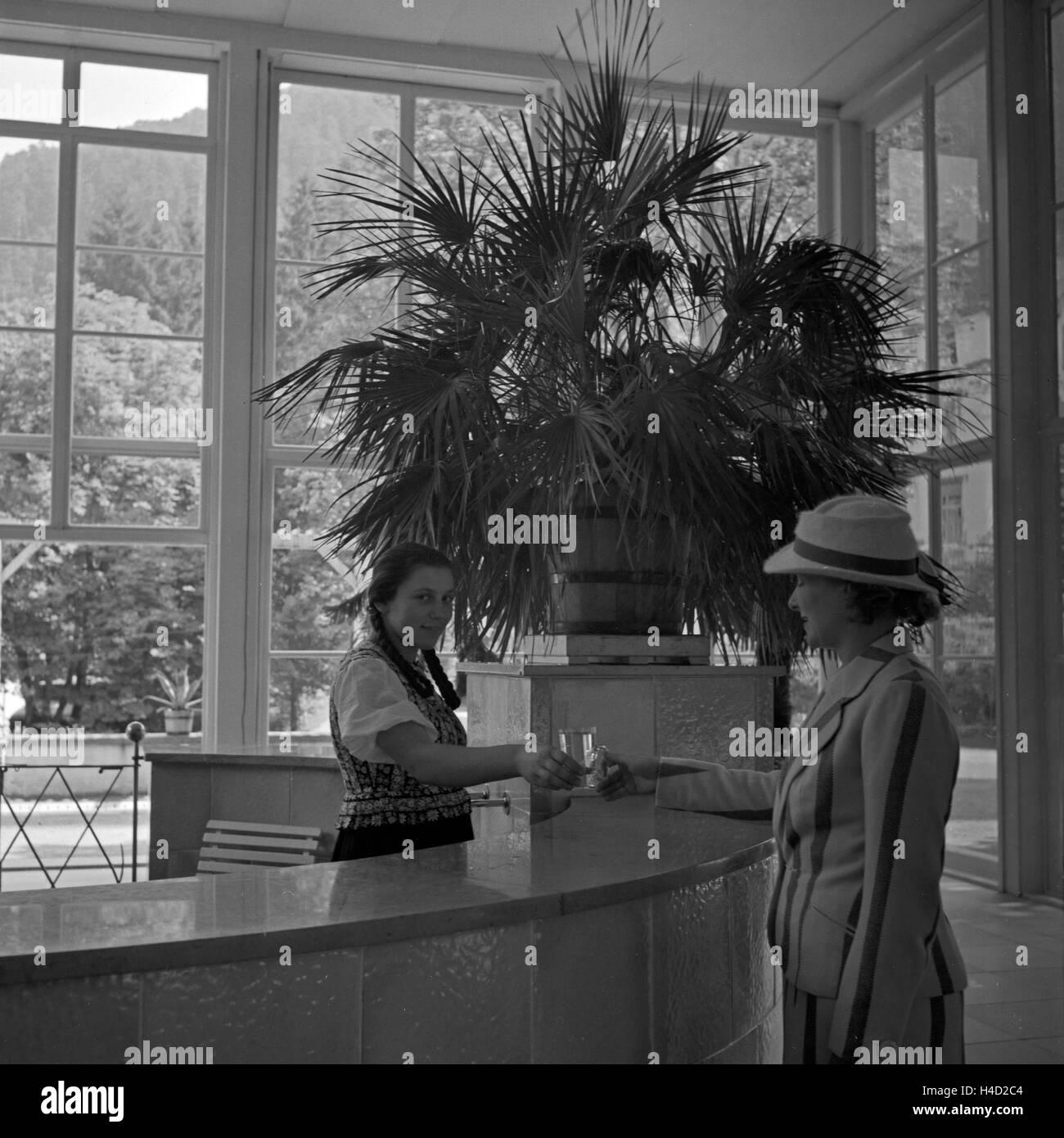 Eine Frau als Gast an der Rezeption eines Kurhotels in Wildbad im Schwarzwald, Deutschland 1930er Jahre. Female - Stock Image