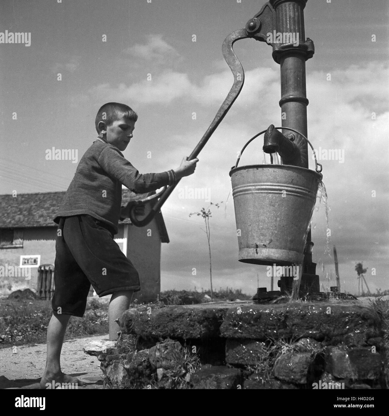 Ein Junge holt Wasser an einem Brunnen in Allenstein in Ostpreußen, Deutschland 1930er Jahre. A boy taking - Stock Image