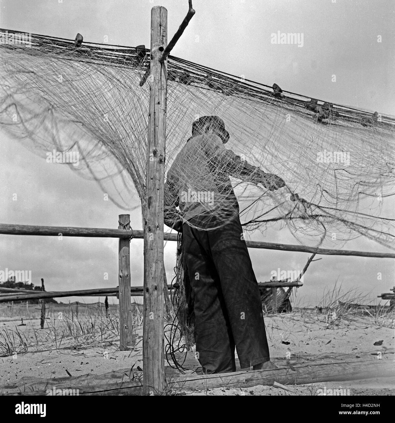 Ein Fischer bei Rositten an der Ostsee sortiert seine Netze, Ostpreußen, Deutschland 1930er Jahre. A fisherman assorting Stock Photo