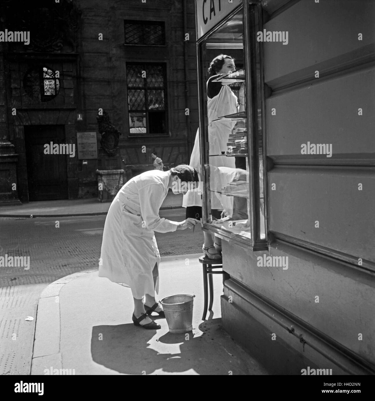 Zwei Angestellte eines Cafes einer Konditorei reinigen den Auslagen Glaskasten in Miesbach, Deutschland 1930er Jahre. Stock Photo