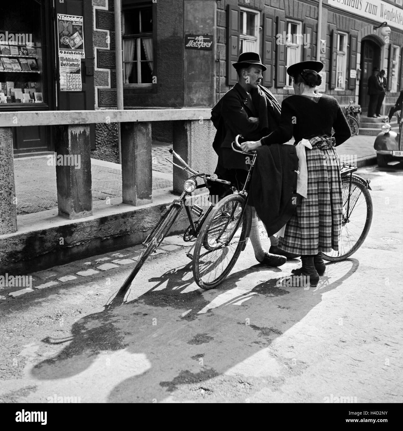 Ein Mann und eine Frau an ihren Fahrrädern unterhalten sich auf der Straße in Miesbach, Deutschland 1930er - Stock Image