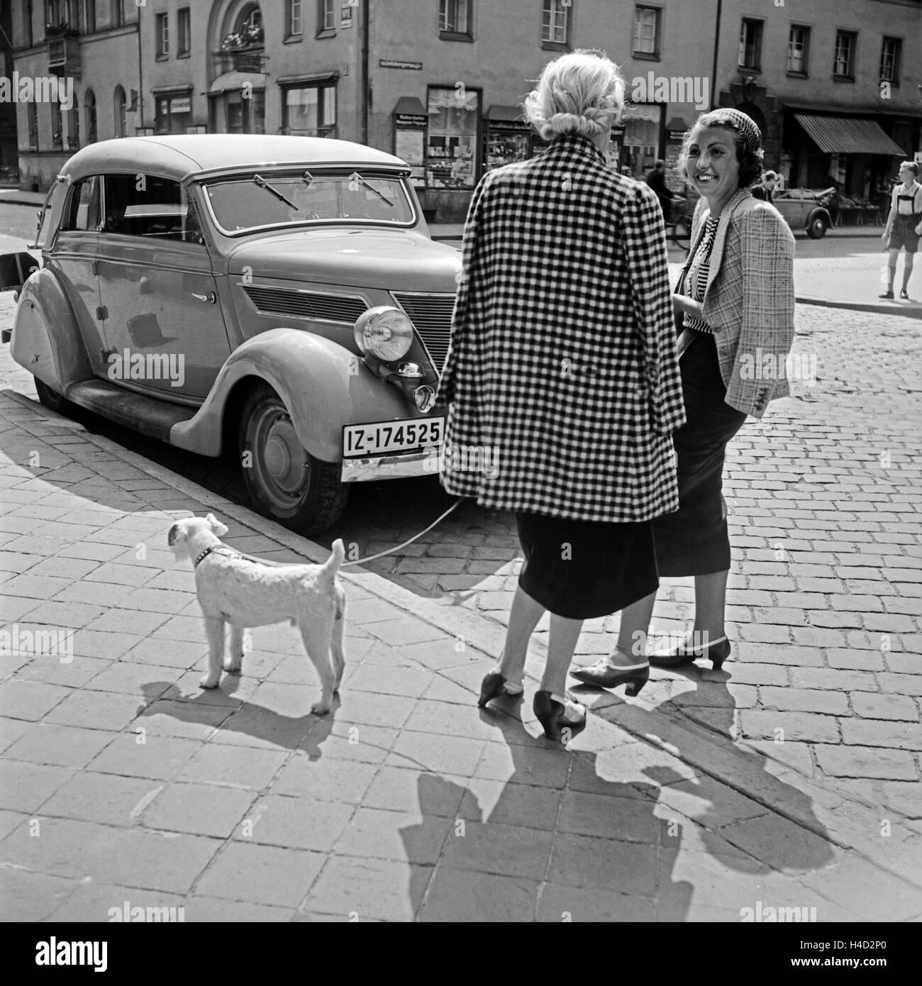 Zwei Frauen aus Miesbach mit einem Hund vor einem Ford V8 bei einem kleinen Schwätzchen, Deutschland 1930er - Stock Image