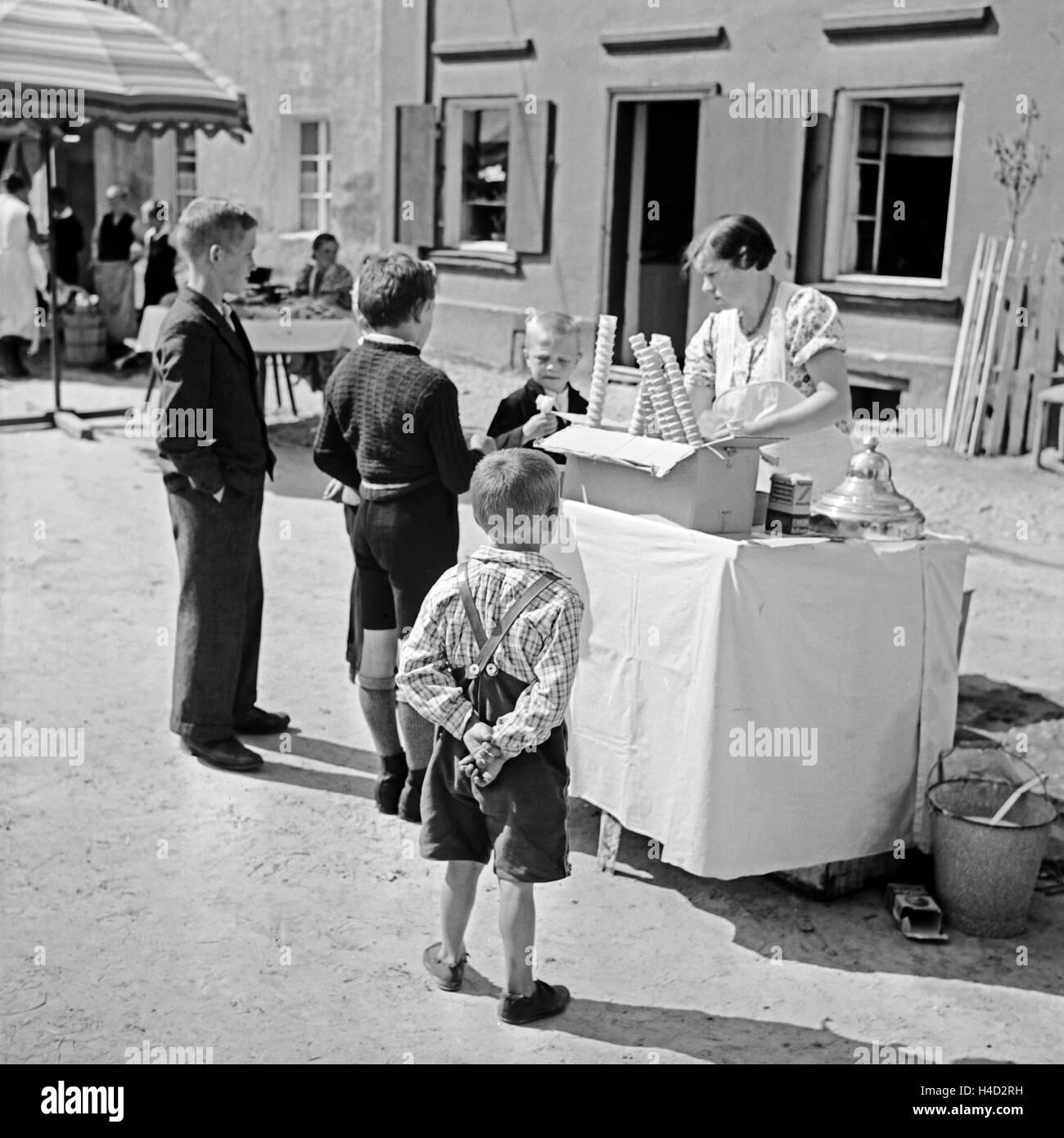Kinder kaufen am Eisstand bei der Eisverkäuferin ein Eis, Deutschland 1930er Jahre. Children buying an icecream - Stock Image