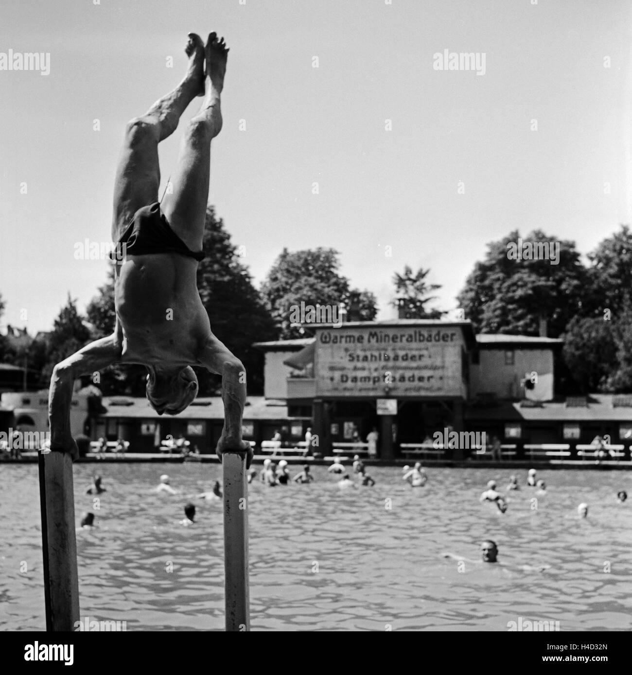 Ein Mann macht Kunststücke am Beckenrand eines Mineralbads, Deutschland 1930er Jahre. A man doing a daring - Stock Image