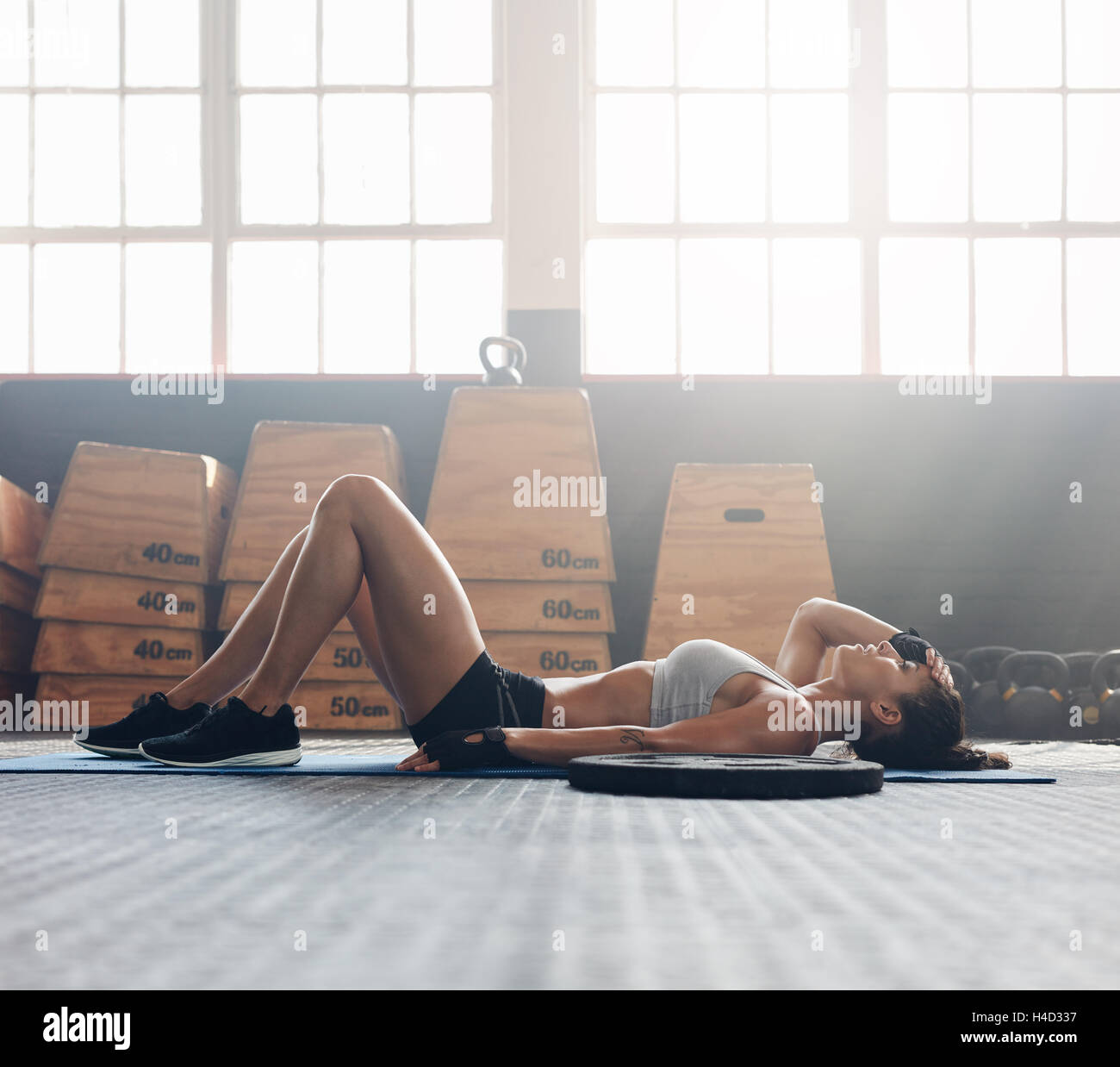 Young woman lying on her back at the gym after her workout. Fitness woman relaxing after exercise session. - Stock Image