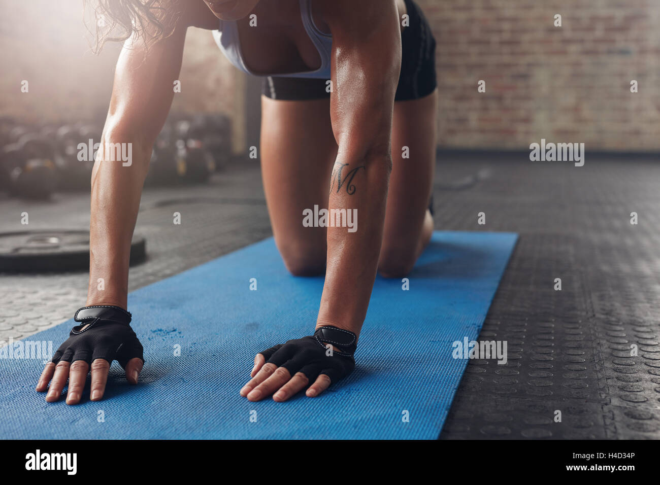 Female on exercise mat doing stretching workout. Focus on hand of a woman on fitness mat. - Stock Image