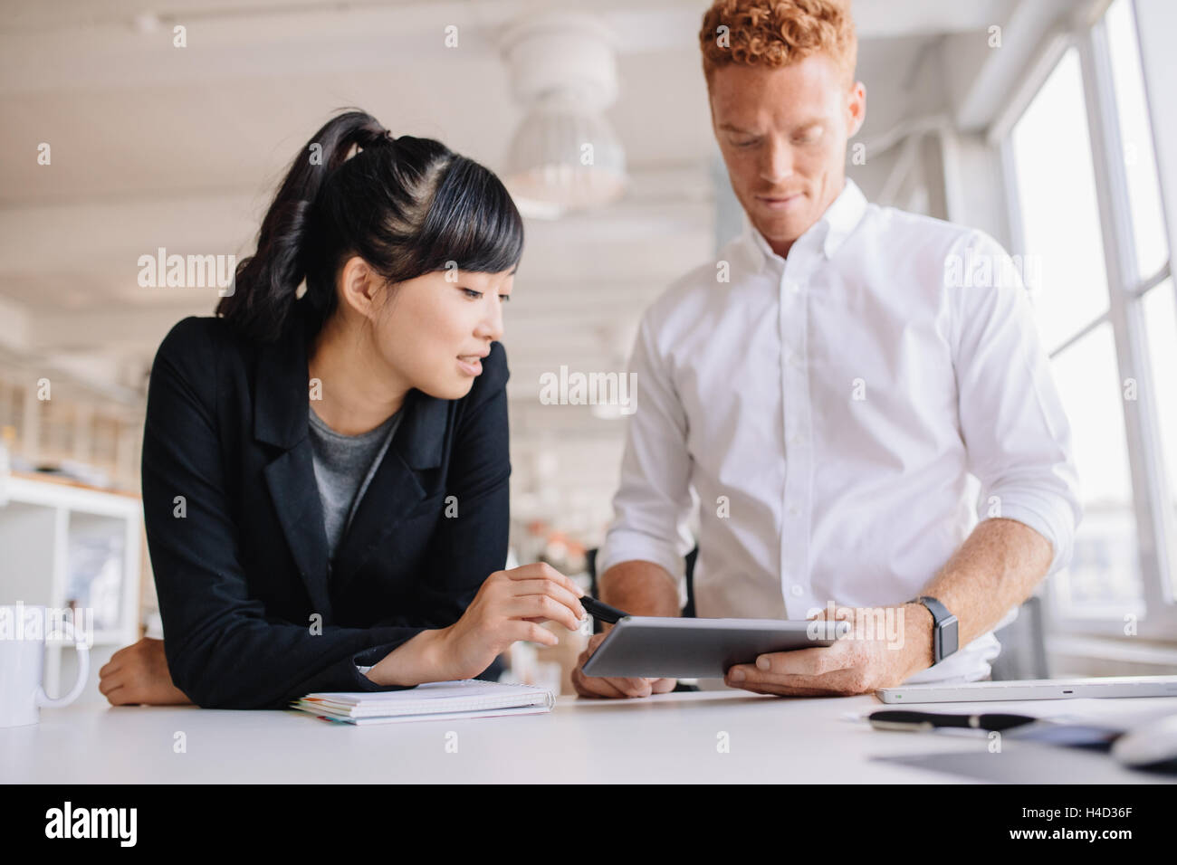 Business people working together on digital tablet in modern office. Business man and woman standing at work desk - Stock Image