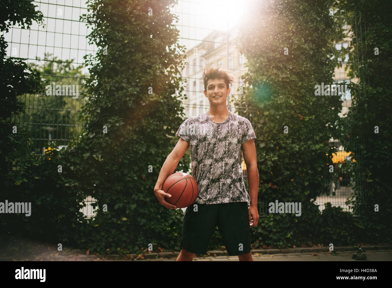 Portrait of young man holding a basketball on outdoor court. Smiling teenage streetball player looking at camera. Stock Photo