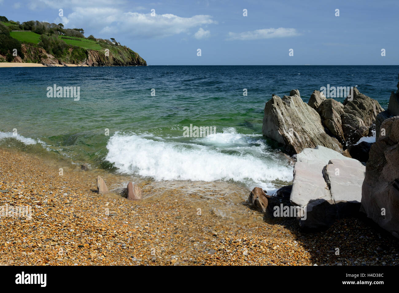 Jagged rocks at the water's edge at Blackpool Sands, South Devon. - Stock Image
