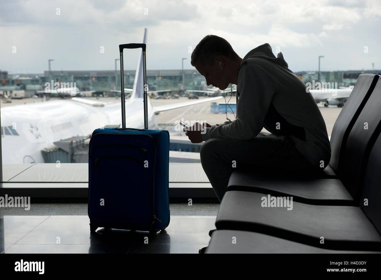A teenager is waiting on an airport and playing with his smartphone - Stock Image