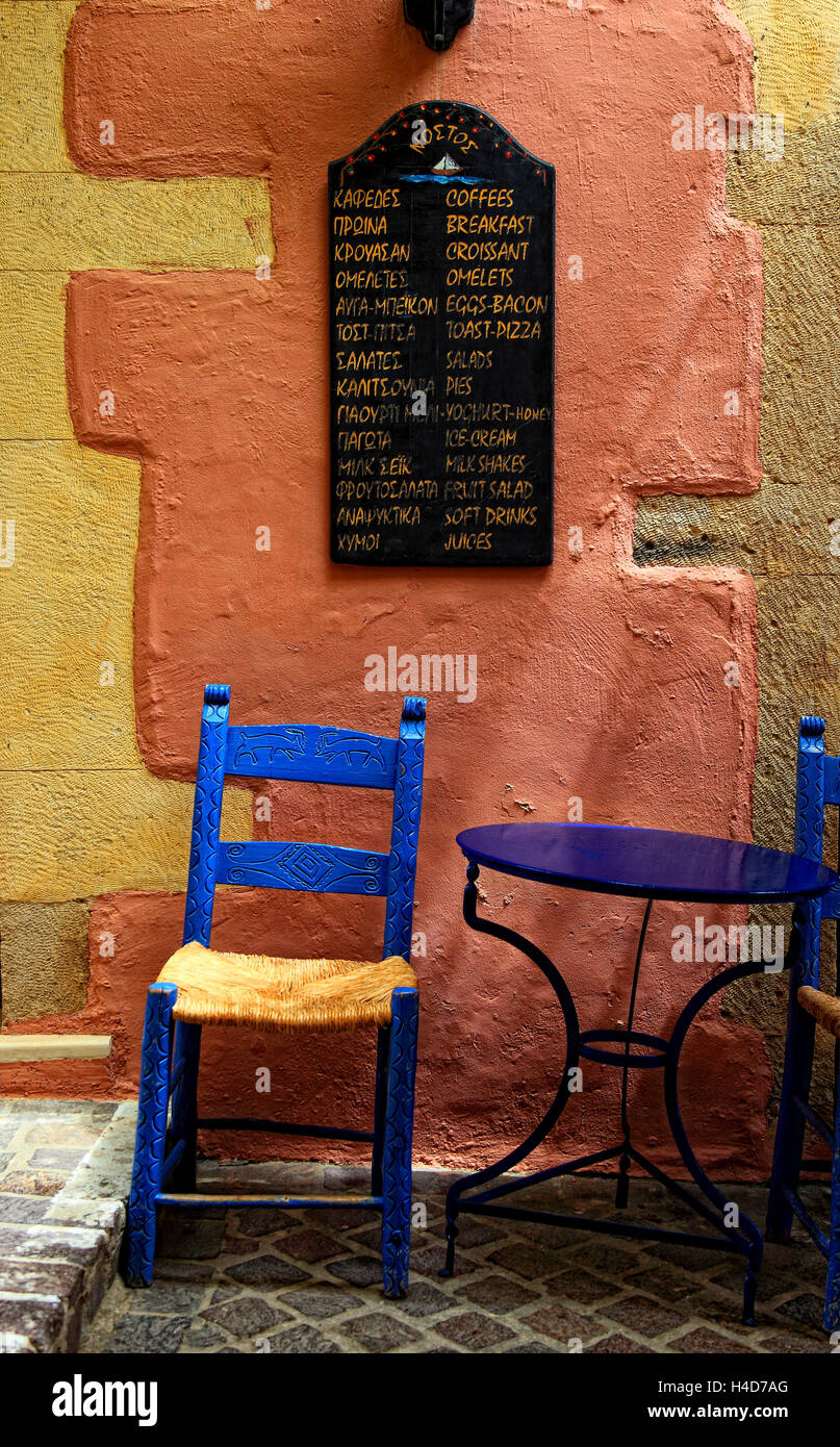 Crete, in the Old Town Canea, blue table and chair and menu card of a small restaurant - Stock Image