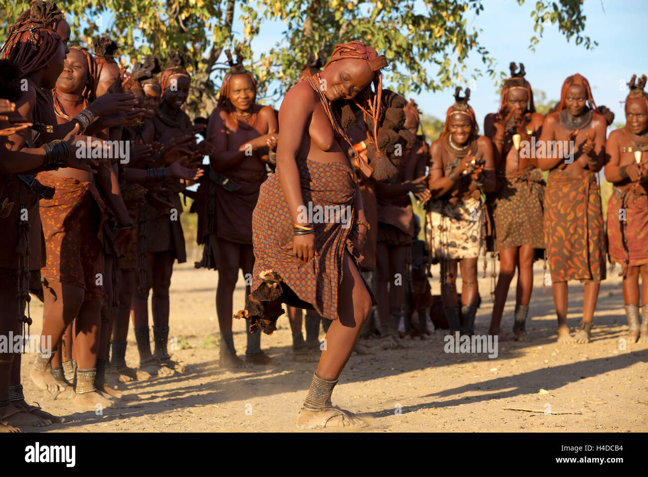 A group of unidentified Himba people perform traditional dance in their village near Opuwo town in Namibia, South - Stock Image