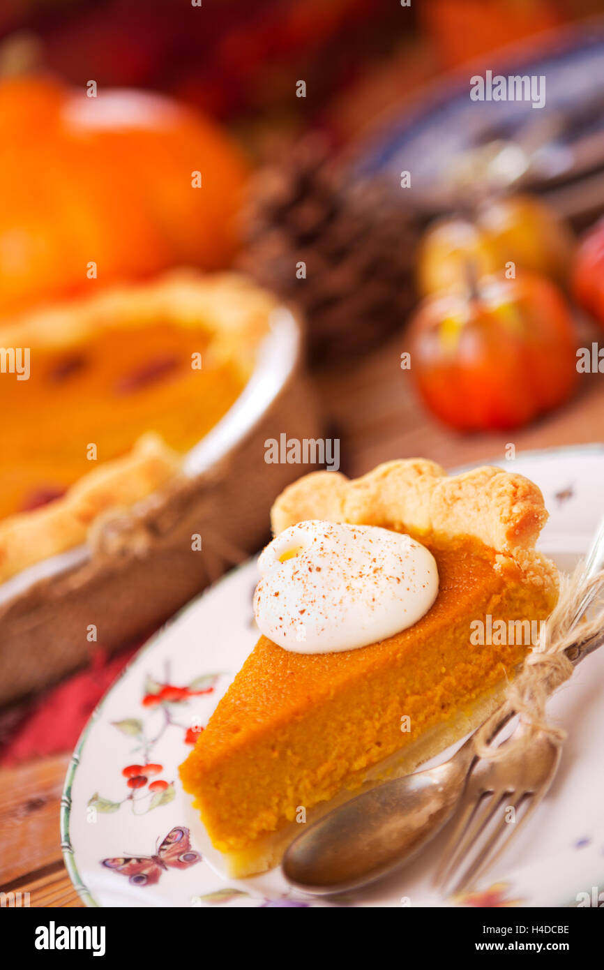 Homemade pumpkin pie on a rustic table with autumn decorations. - Stock Image