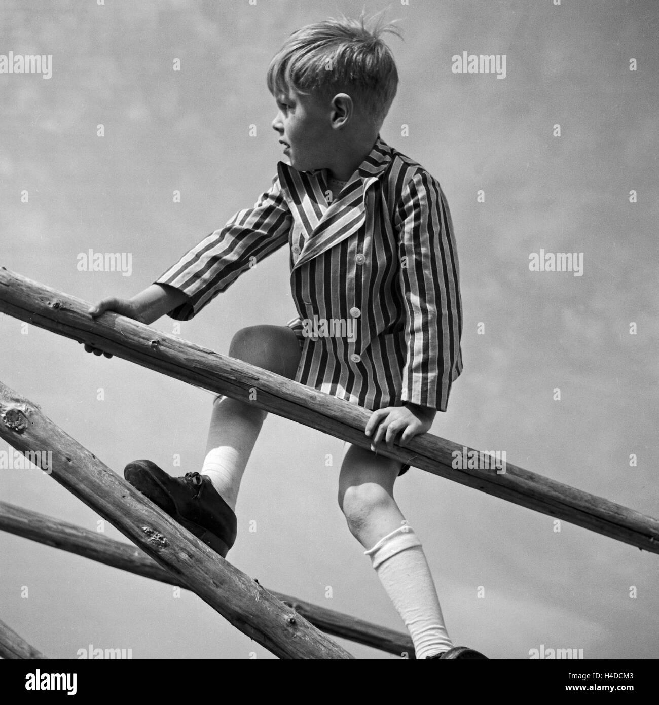 ein kleiner junge spielt und klettert auf einem holzgerüst stock