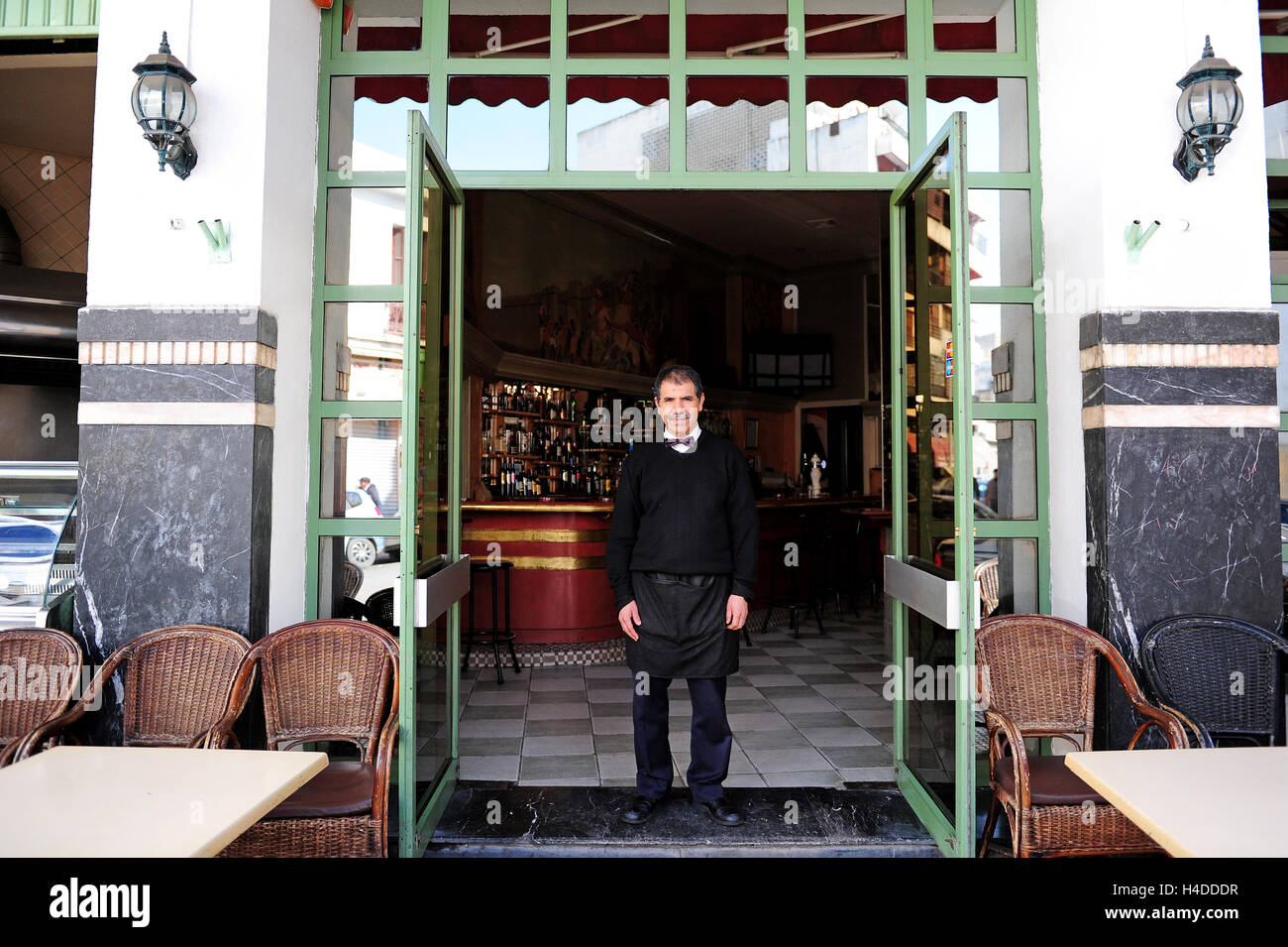 A waiter has his picture taken in front of a French-style café opposite the Cinema Rialto in Casablanca - Stock Image