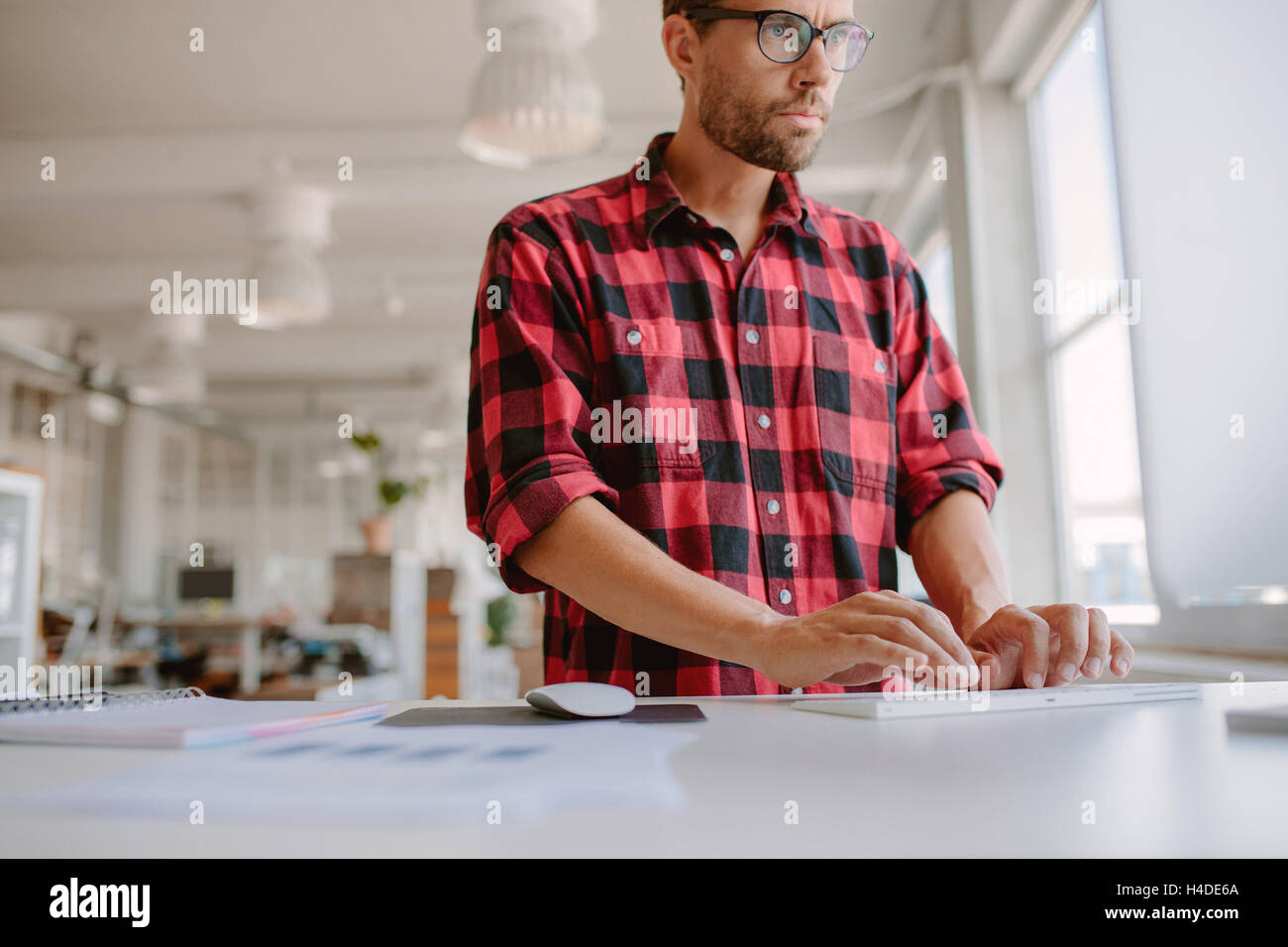 Shot of young man standing at his desk and working on computer. Businessman using computer in modern office. - Stock Image