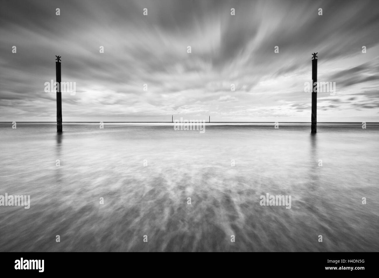 Navigation guide posts in the North Sea off the Northumberland coast on an overcast day, long exposure creative - Stock Image