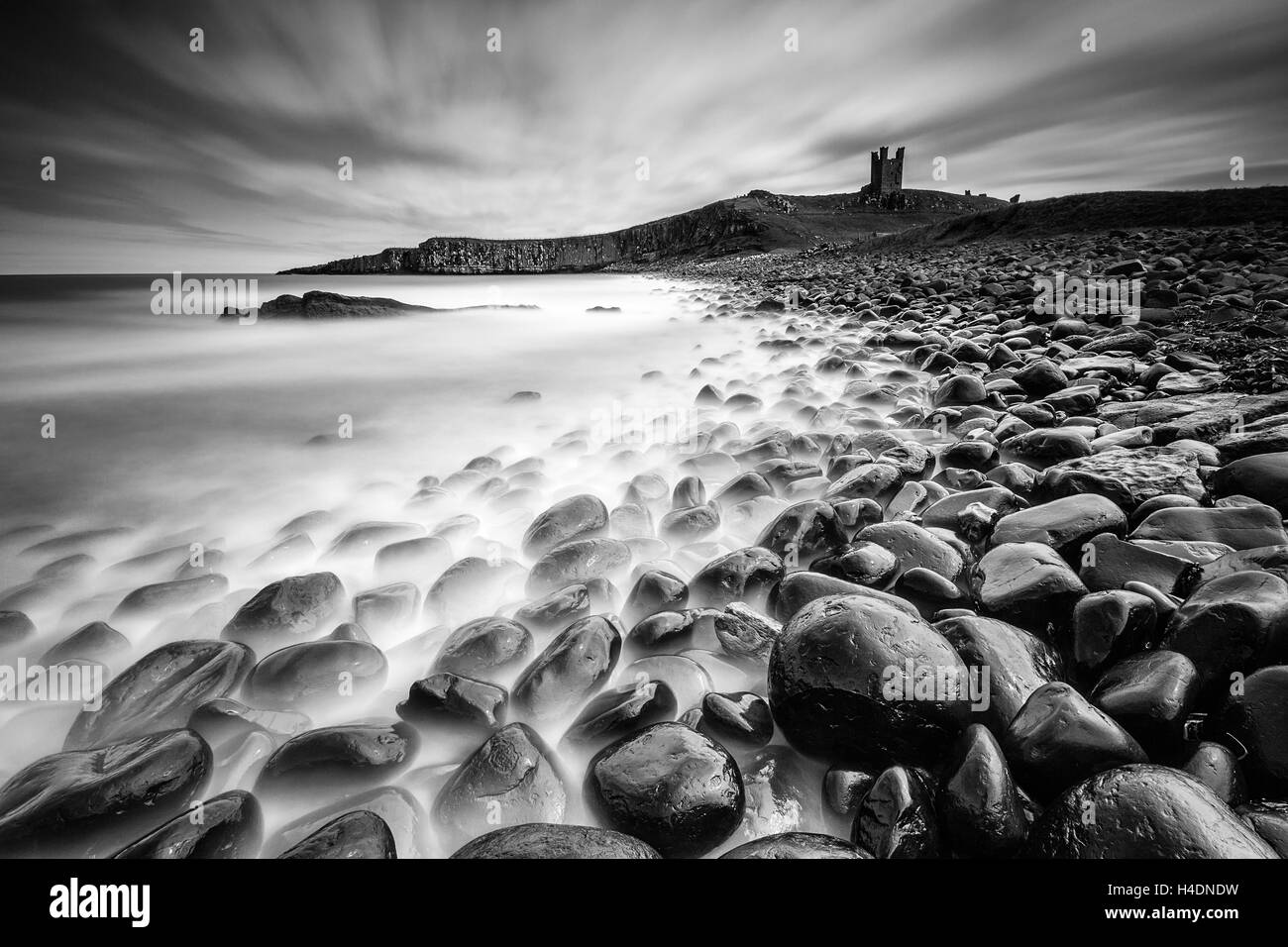 The ruins of Dunstanburgh Castle at Embleton Bay in Northumberland, long exposure from the boulder field rocky shore - Stock Image