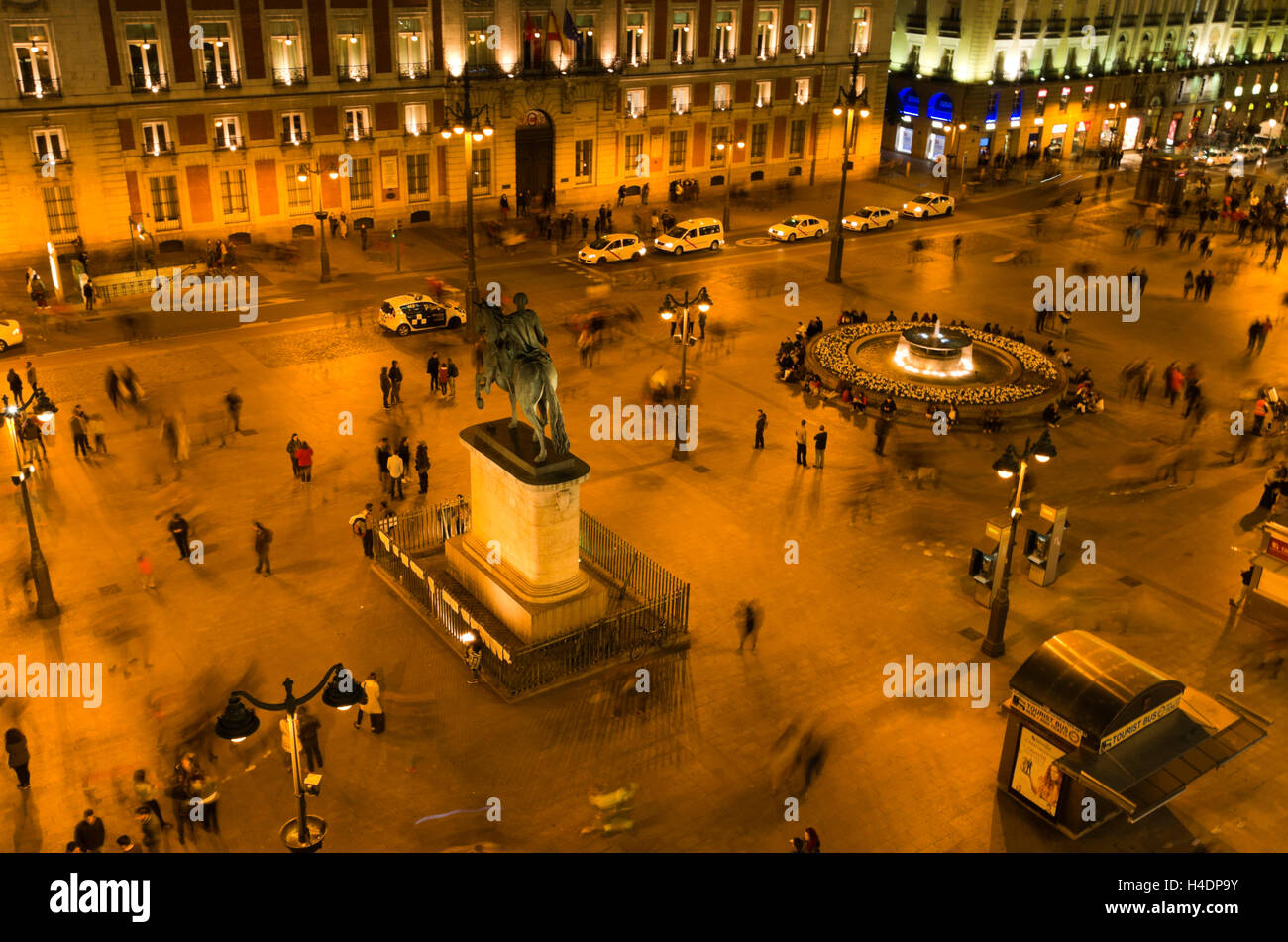 Puerta del Sol, hundreds of people mill around the plaza at night. Stock Photo