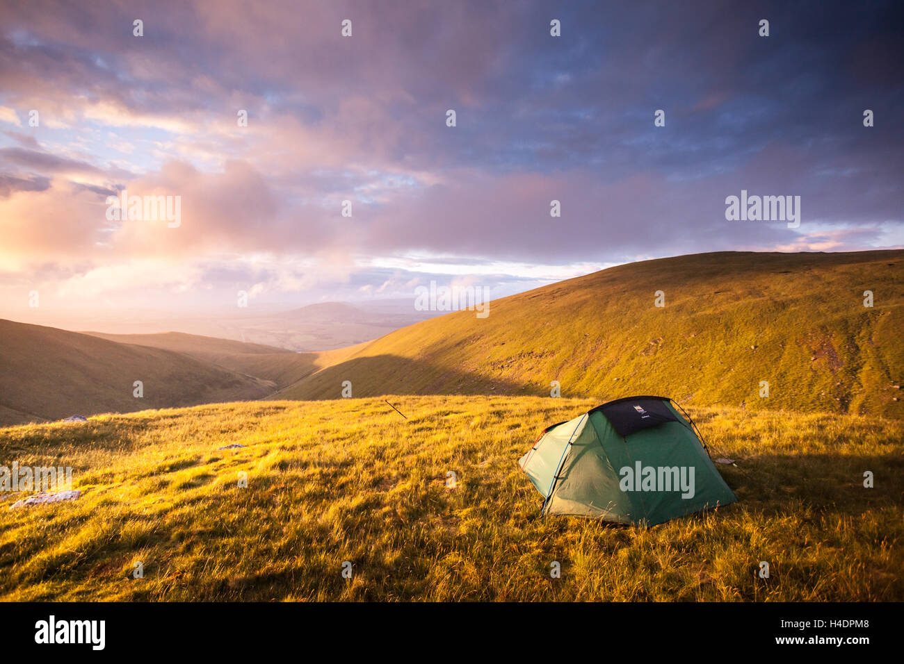 Wild camp little green tent on the side of Blencathra mountain at sunrise in the English Lake District - Stock Image