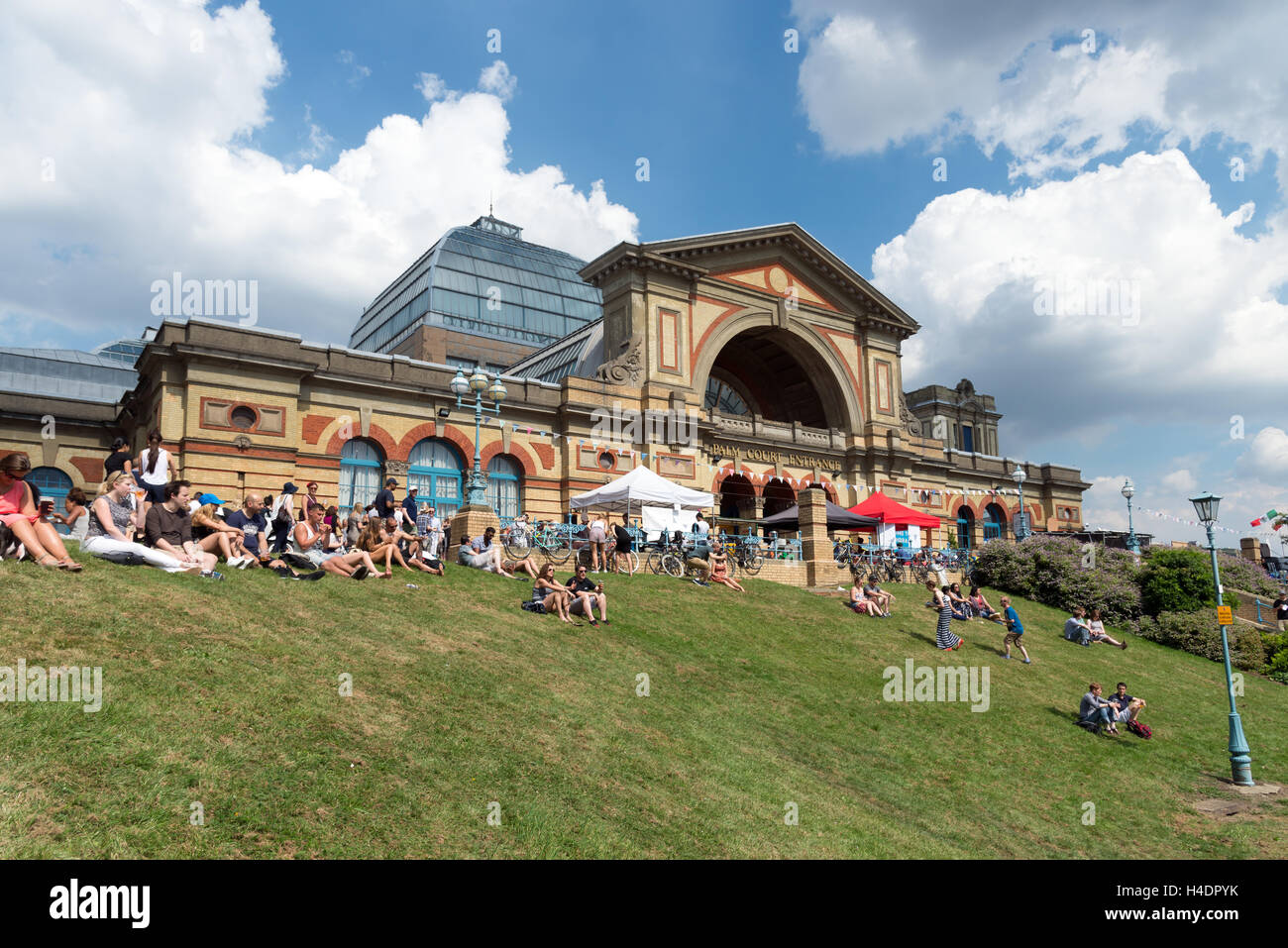 People sitting on grass outside Alexandra Palace during Alexandra Park Festival, Haringey, London, England, UK - Stock Image