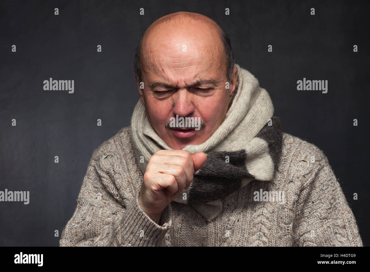 Elderly man is ill from colds or pneumonia. elderly man in a sweater and a woolen scarf strongly coughs - Stock Image