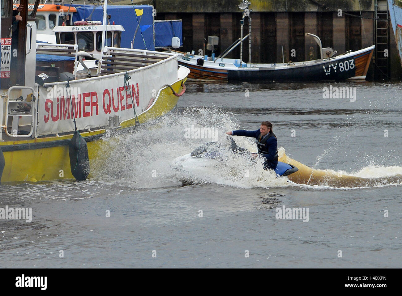 A stuntman crashes a jet ski into a boat in Whitby harbour as Jeremy Clarkson's new show The Grand Tour films - Stock Image