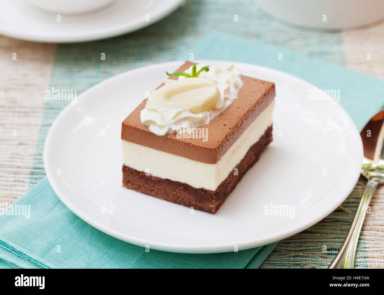 Three chocolate mousse cake on a white plate - Stock Image