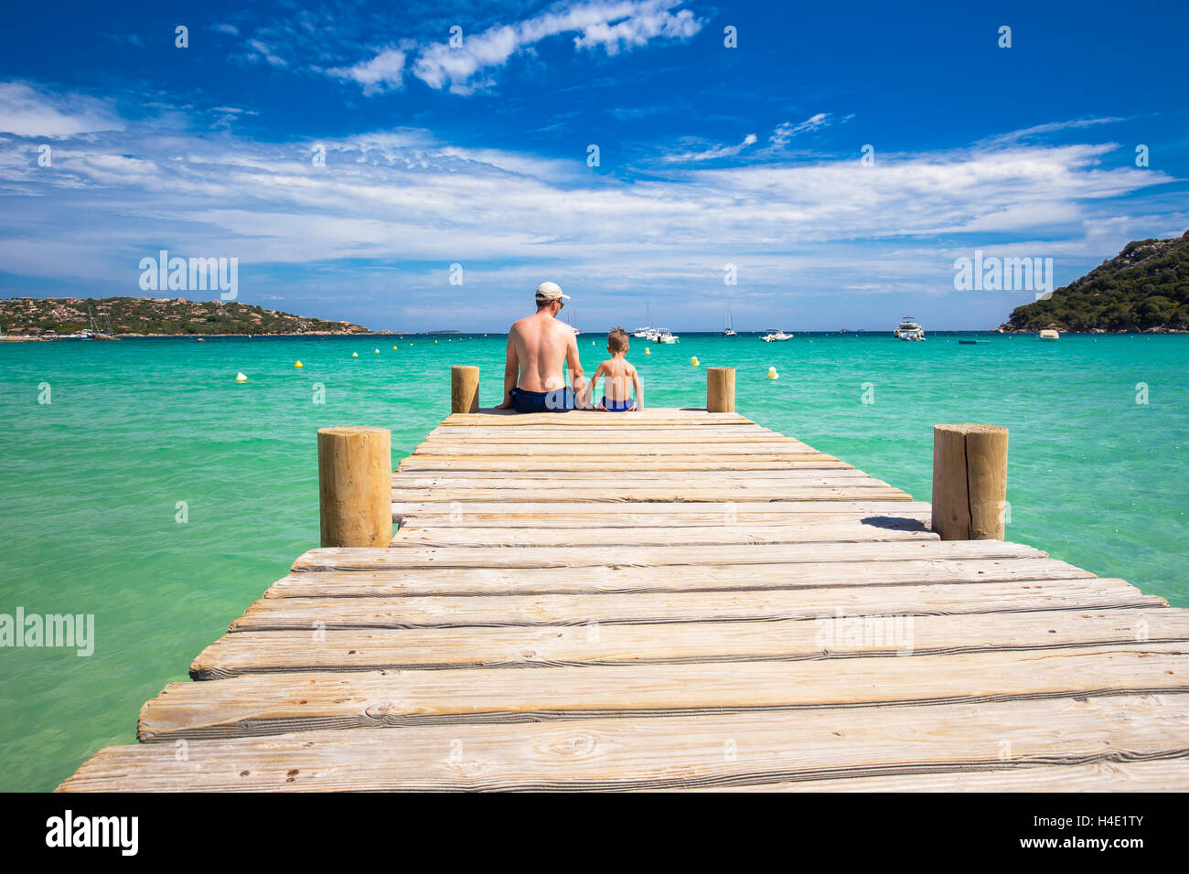 Father and his little son enjoying sea on Santa Giulia beach with tourquise clear water and pine trees, Corsica, - Stock Image
