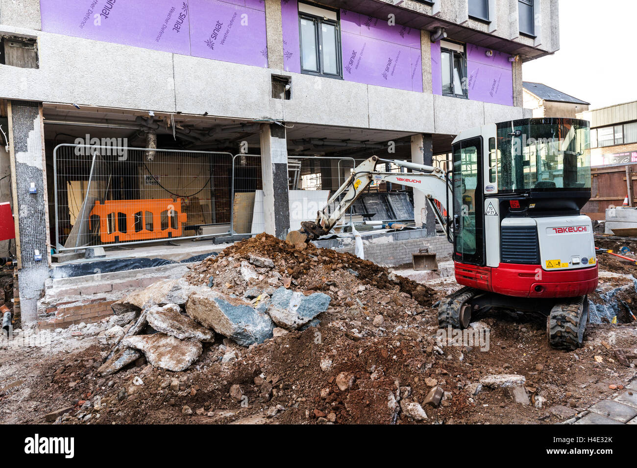 Digger and pavement being dug up during building renovations, Cardiff, UK - Stock Image