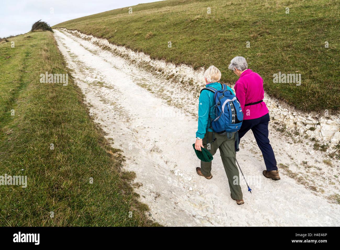 Two people walking on chalk track, Compton Down, Isle of Wight, UK - Stock Image