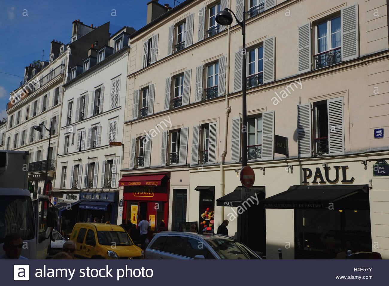 Delivery vans parked outside white buildings with shuttered windows and shops on the ground level along Rue Lepic - Stock Image