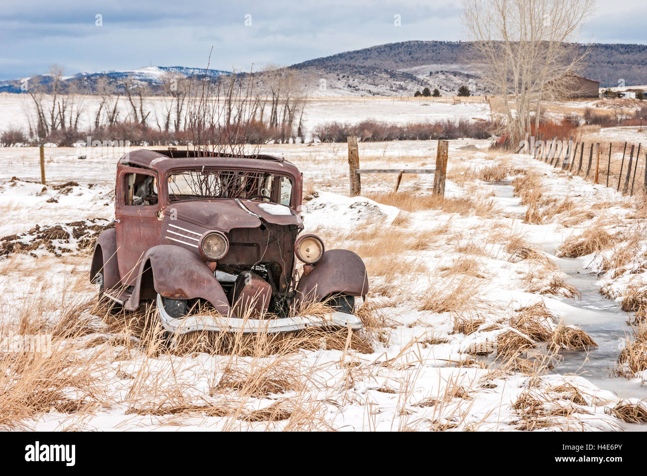 Rusty, dilapidated, abandoned vehicle in a field in rural America on a winter day - Stock Image
