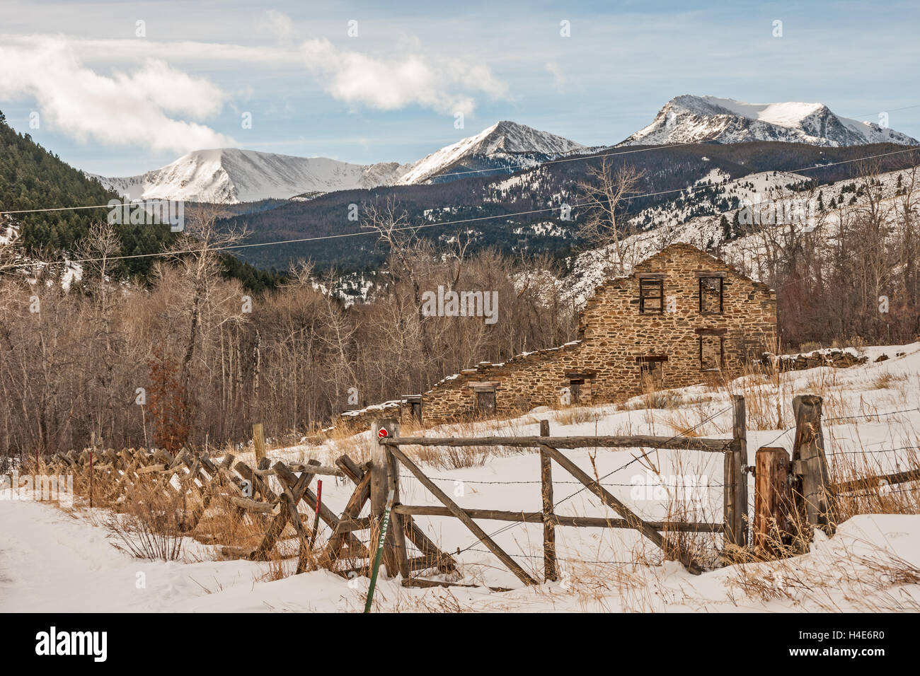 Remains of a twenty-stamp gold mill built in 1883 in Montana on a winter day with the Tobacco Root Mountains in - Stock Image