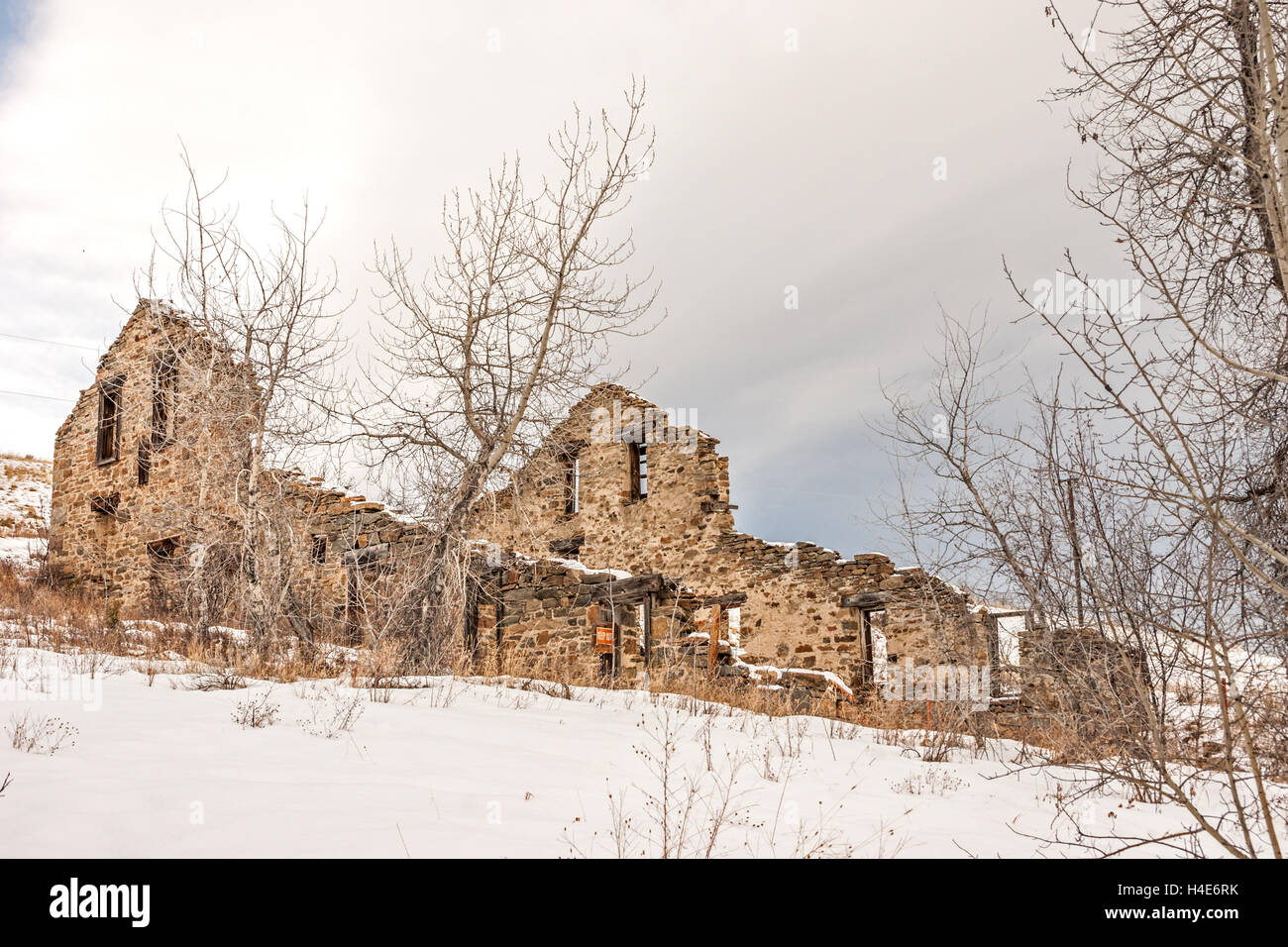 Remains of a twenty-stamp gold mill built in 1883 in Montana on a winter day - Stock Image