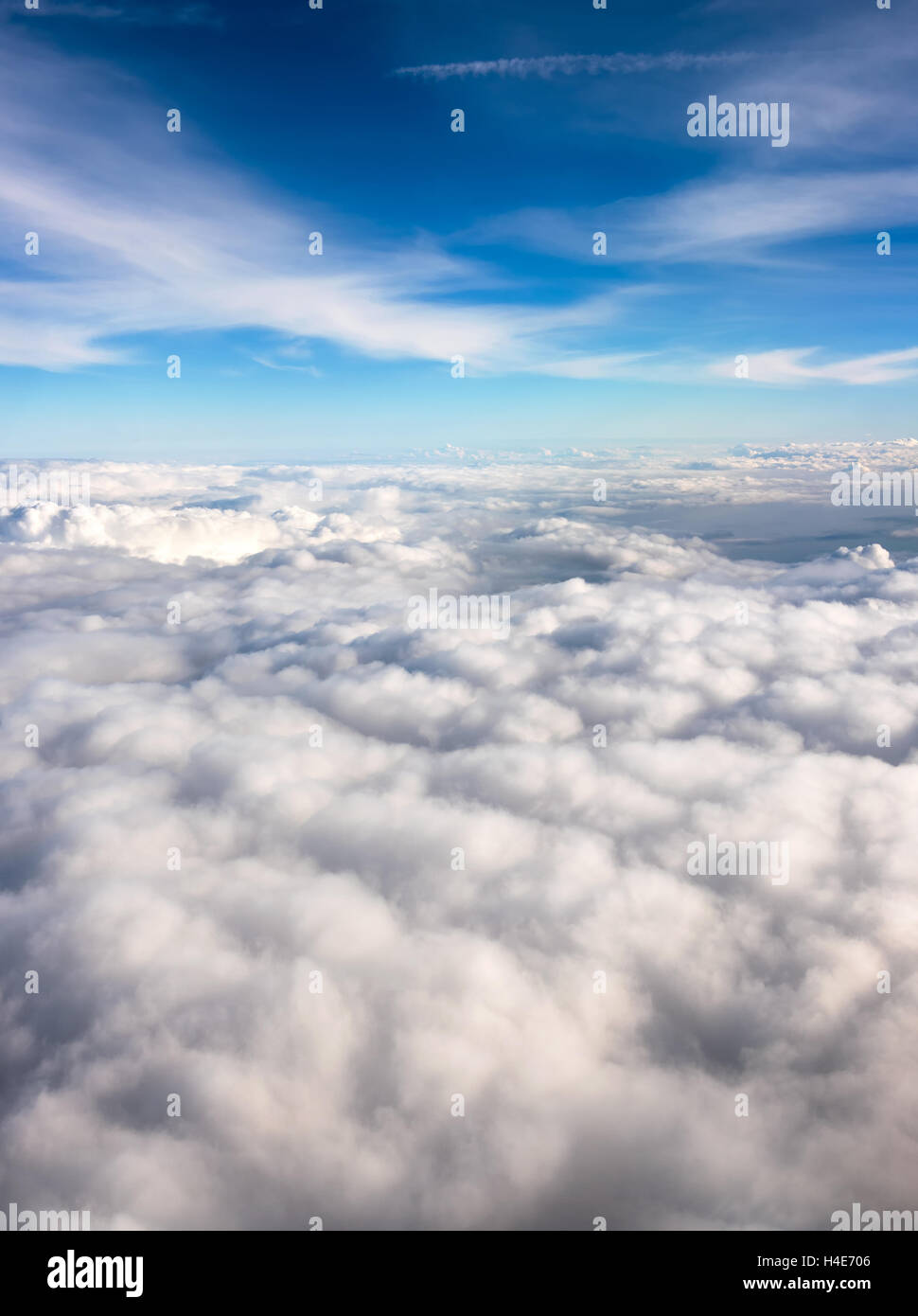Flying high above a layer of dense white fluffy clouds in clear blue sky and sunshine in a travel concept - Stock Image