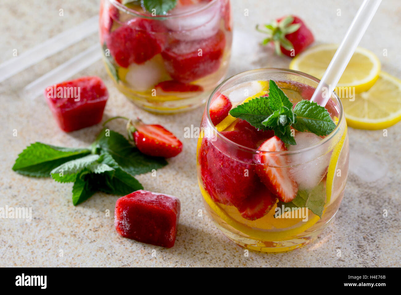 Tradition Summer mojito drink with lemon and mint with copy space on brown stone background. - Stock Image