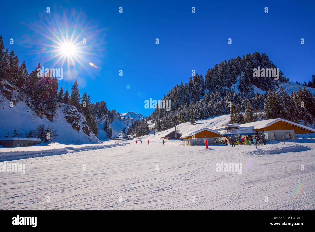 Skiers skiing on ski slopes on the top of the Hoch Ybrig resort, Switzerland - Stock Image