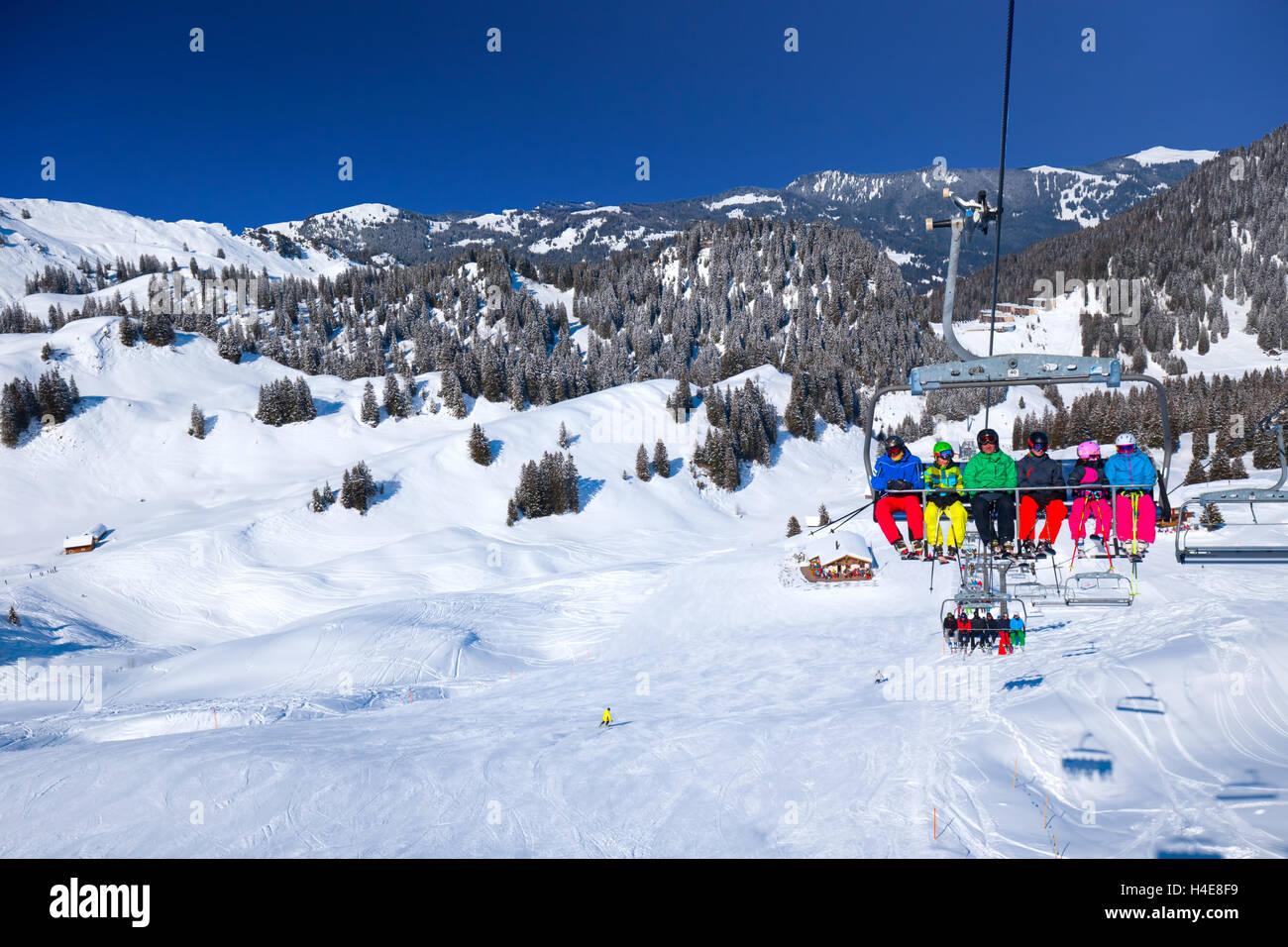 Skiers on chair lift in the Hoch-Ybrig ski resort, Schwyz, Switzerland - Stock Image