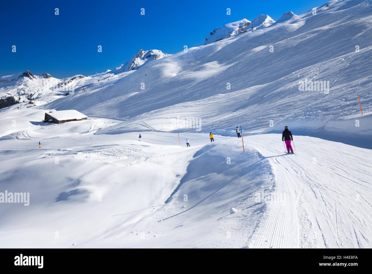 Skiers skiing on the top of the Hoch-Ybrig ski resort, Switzerland - Stock Image